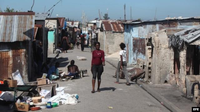 Una mujer caminia por un barrio en Puerto Principe, Haití.