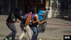 Un grupo de manifestantes se defienden de la policía durante una protesta en Venezuela.
