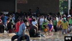 Personas cargan productos saqueados a tiendas hoy en el puerto de Acapulco (México), tras el paso del huracán Manuel