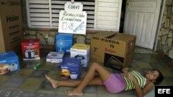 """ARCHIVO. Una joven descansa en el portal de su casa que donde se muestran algunas cajas de los efectos electrodomésticos de la llamada """"revolución energética"""" en Cuba."""