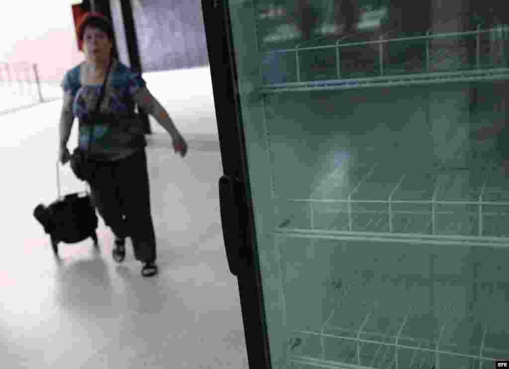 Una mujer ingresa a un supermercado con una nevera desabastecida hoy, viernes 1 de febrero de 2013, en Caracas (Venezuela).