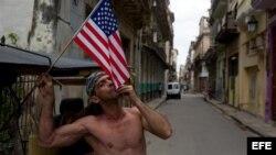 Un cubano besa una bandera norteamericana en una calle de La Habana Vieja. EFE