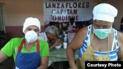 """Dos mujeres del proyecto """"Capitán Tondique"""" sirven alimentos en un almuerzo a desamparados en Matanzas."""