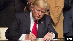 El presidente estadounidense, Donald J. Trump, firma el memorando presidencial sobre la política con Cuba tras finalizar su discurso en el teatro Manuel Artime de la Pequeña Habana, en Miami.