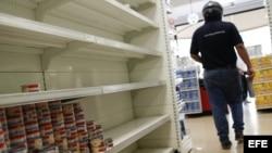 Un cliente recorre un pasillo con estanterías desabastecidas en un supermercado.