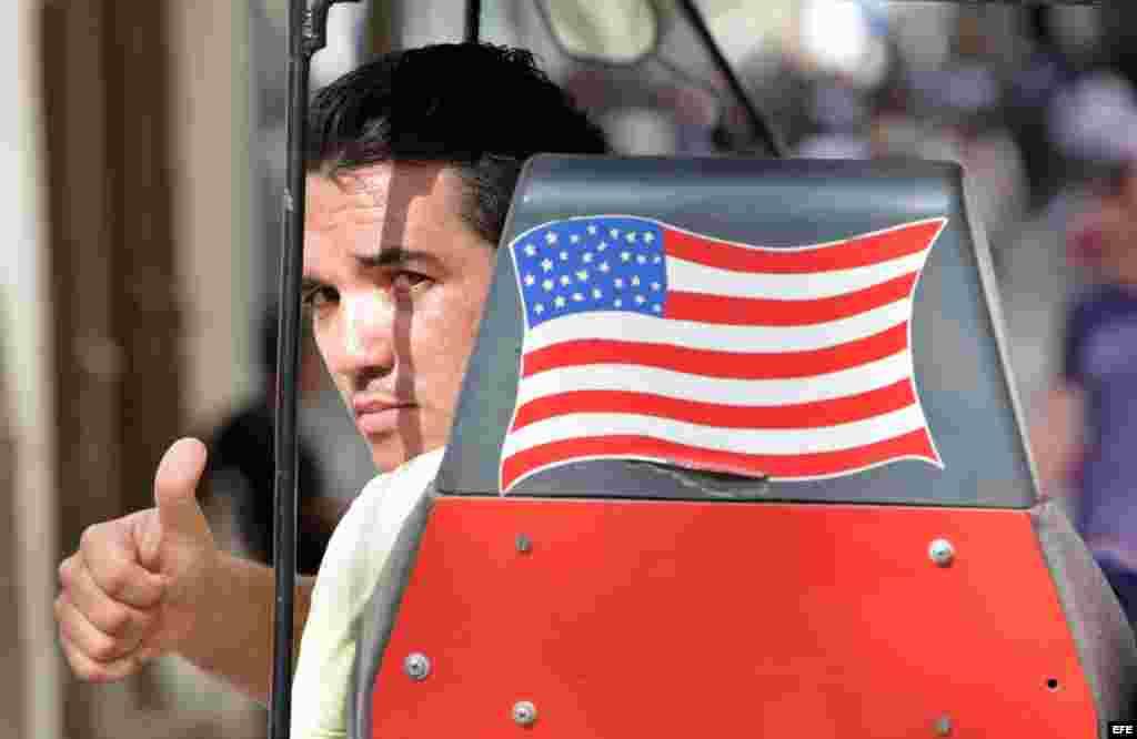 Un hombre saluda desde una bicitaxi con la bandera de EEUU.