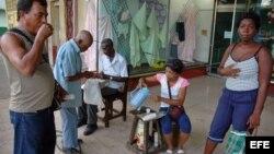 Varias personas toman café en el portal de una tienda, en La Habana, Cuba.