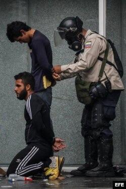 Agentes de la Policía Nacional Bolivariana detienen a manifestantes.