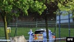 Varios forenses británicos inspeccionan el lugar donde un soldado murió y otros dos resultaron heridos en un ataque con machete en Londres, Reino Unido hoy, miércoles 22 de mayo de 2013