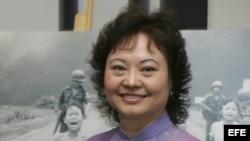 Kim Phuc posa junto a la famosa fotografia de la guerra de Vietnam que ella protagonizó.