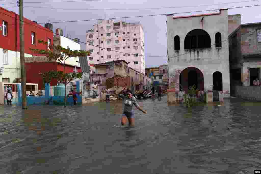 Una mujer cruza una calle inundada por las penetraciones del mar hoy, sábado 23 de enero de 2016, en La Habana (Cuba). EFE/Alejandro Ernesto