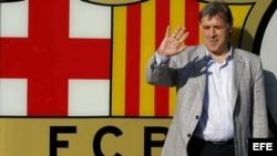 El nuevo entrenador del F.C.Barcelona, el argentino Gerardo 'Tata' Martino, posa ante el escudo barcelonista.