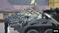 Un soldado ucraniano hace guardia junto a varios vehículos armados en una base militar en Lviv (Ucrania)