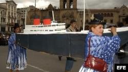 Mujeres aimaras llevan un barco construido con cartón, durante un desfile cívico militar en la Plaza de Los Héroes de La Paz, Bolivia.