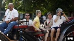 HAB04. LA HABANA (CUBA), 08/05/2012.- Un grupo de turistas pasea en un coche tirado por caballos hoy, martes 8 de mayo de 2012, por una calle de La Habana (Cuba), día en que se inaugura en Cayo Santa María, en el centro de la isla, la Feria Internacional