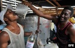 Dos hombres beben y bromean mientras venden cerveza y ron en los carnavales de Santiago de Cuba.