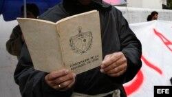 Un hombre lee la Constitución de la República de Cuba delante de una pancarta que pide cambios para el país. (Archivo)