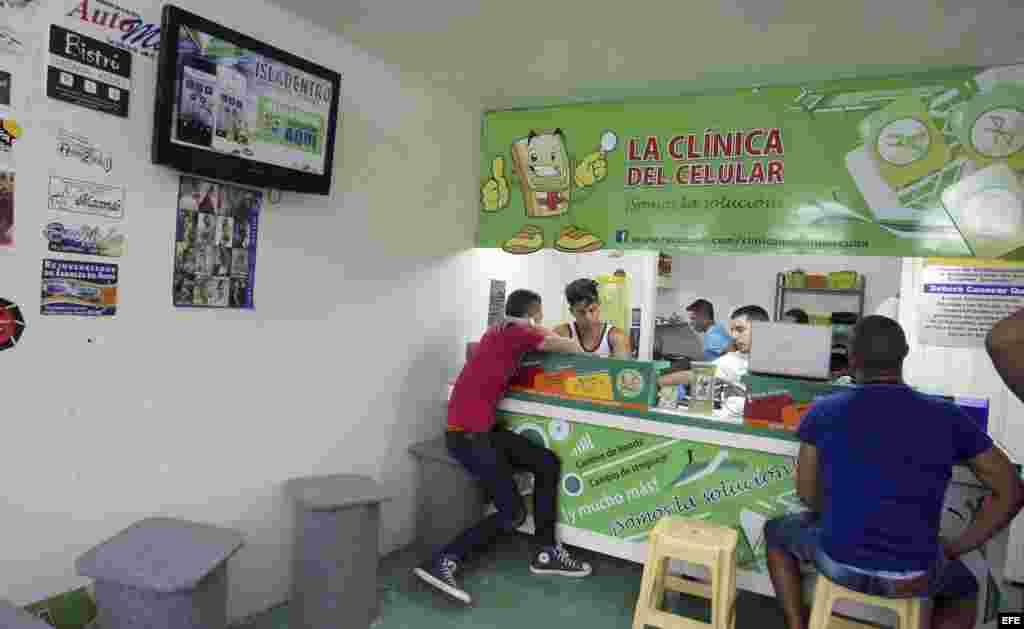 Varios jóvenes atienden a los clientes en un negocio de reparación de móviles, en La Habana.