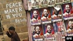 """Una mujer keniana pasa junto a un grafiti que dice """"El pacificador eres tú"""", en el suburbio de Kibera en Nairobi, Kenia."""
