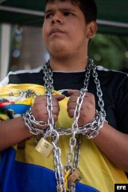 Un estudiante encadenado participa en una protesta a pocos metros de la sede de la embajada de Cuba en Cararcas