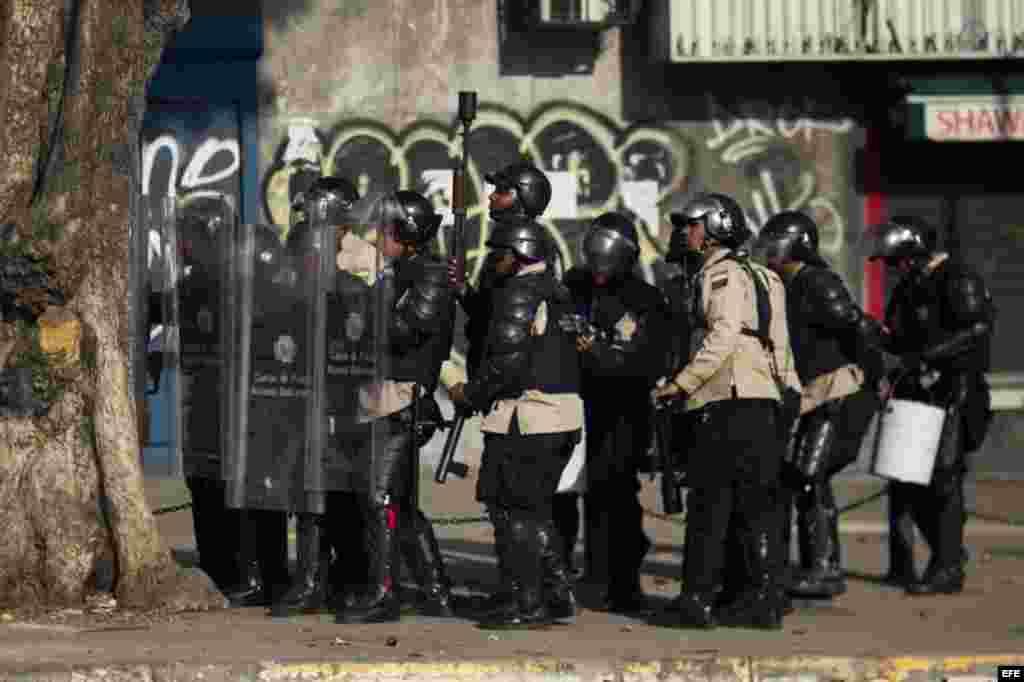 Un grupo de manifestantes se defienden de la policía durante una protesta
