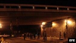 Los cuerpos de cuatro jóvenes decapitados se observan atados y colgando de un puente hoy, domingo 22 de agosto de 2010, en la autopista México-Acapulco.
