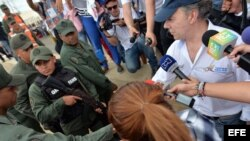Juan Manuel Santos saluda a miembros de la Guardia Nacional Bolivariana en su visita a un paso fronterizo. EFE.