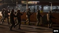 """Miembros de la Guardia Nacional Bolivariana (GNB) permanecen alerta hoy, lunes 17 de febrero de 2014, durante protestas registradas en el sector Los Ruices, cerca al canal de televisión estatal """"Venezolana de Televisión"""" (VTV), en Caracas (Venezuela)."""