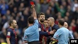 El árbitro Pérez Lasa muestra la tarjeta roja al portero del Barcelona Víctor Valdés (2d) que protesta, mientras su compañero, el defensa Gerard Piqué (3i), intenta frenarlo ante la mirada del centrocampista Andrés Iniesta (i), durante el partido frente a