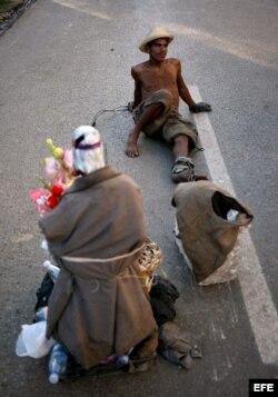 Un hombre toma un descanso mientras arrastra una piedra y una imagen de San Lázaro el domingo 16 de diciembre de 2012, durante una procesión en el Santuario de El Rincón, Cuba.