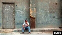 Un jombre permanece sentado junto a un cartel alusivo al presidente cubano Fidel Castro, en La Habana.