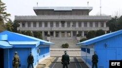 Soldados surcoreanos (de espaldas a la cámara) observan a un soldado norcoreano (al fondo, entre las columnas) en la zona desmilitarizada donde en 1953 se firmó el armisticio entre las dos coreas en Panmunjom (Corea del Sur) hoy, jueves 28 de marzo de 2014.