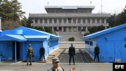 Soldados surcoreanos (de espaldas a la cámara) observan a un soldado norcoreano (al fondo, entre las columnas) en la zona desmilitarizada donde en 1953 se firmó el armisticio entre las dos coreas en Panmunjom (Corea del Sur) hoy, jueves 28 de marzo de 201