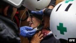 Un manifestante herido es atendido por personal de emergencia, durante los bloqueos en rechazo a las elecciones de la Constituyente.