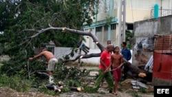 Varias personas talan árboles derribados por el huracán Sandy en el poblado de Caimanera, en la provincia de Guantánamo (Cuba).
