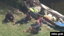 Cuatro inmigrantes cubanos descansan junto a su bote en el patio de una casa de Palmetto Bay.
