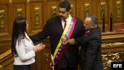 Nicolás Maduro (c), recibe la banda presidencial de manos del presidente de la Asamblea Nacional, Diosdado Cabello (d), y de la hija del fallecido presidente venezolano Hugo Chávez, María Gabriela Chávez (i).
