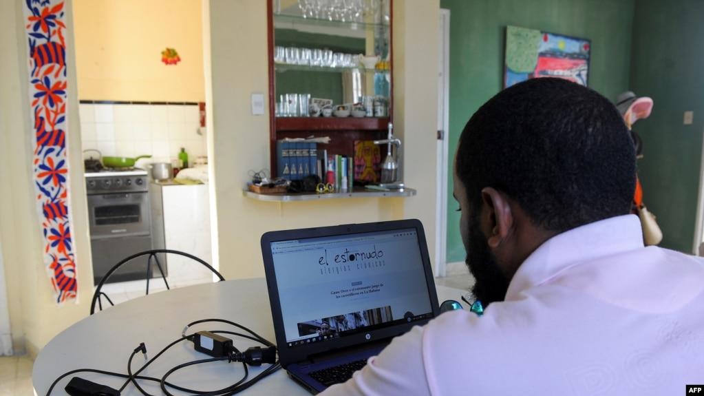 """El periodista Abraham Jimenez, del medio independiente """"El Estornudo"""", escribe en su laptop desde su casa en La Habana. (Archivo)"""