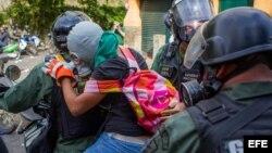 Miembros de la Guardia Nacional Bolivariana detienen a una joven