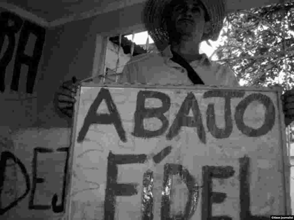 Agustín Cervantes, activista de UNPACU y preso político, enarbola un cartel anticastrista.