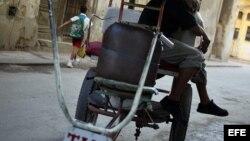 Un bicitaxista toma una siesta sentado en su vehículo en una calle de La Habana (Cuba).