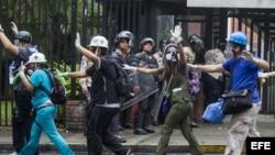 Un grupo de paramédicos voluntarios caminan con sus manos en alto en medio de los intentos de la Policía Nacional Bolivariana (GNB) por dispersar un grupo de manifestantes opositores al Gobierno.
