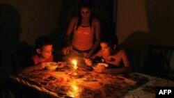 Niños comen a la luz de una vela durante un apagón en Cuba en el año 2009.