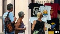 Un grupo de turistas observa varias camisetas entre las que destacan varias con la imagen del Che Guevara, en La Habana, Cuba.