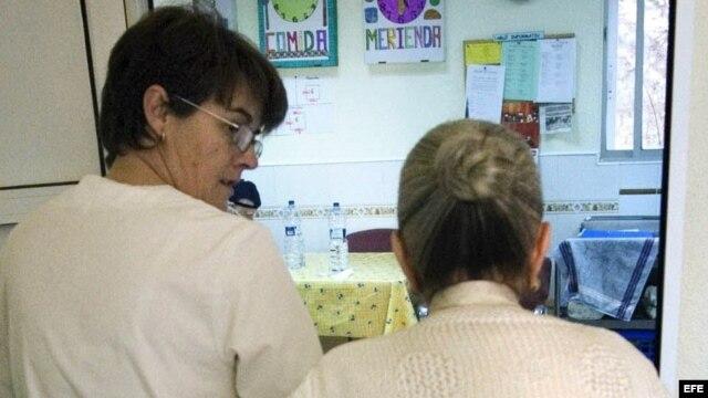 """Una auxiliar acompaña al comedor a una enferma de alzheimer en el centro de día """"La Pineda"""" en Castellón."""