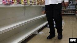 Un hombre camina por un pasillo de supermercado frente a estanterías desabastecidas, en Caracas (Venezuela).