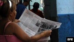 """Una mujer lee el diario oficial Granma. El gobierno cubano fustiga a los periodistas independientes través de la sustracción de recursos y """"arrestos breves"""" que les impiden hacer su trabajo."""