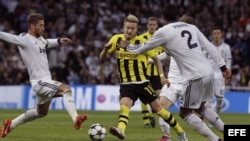 El defensa del Real Madrid, Sergio Ramos (i), lucha el balón con Marco Reus (c), del Borussia Dortmund, durante el partido correspondiente a la vuelta de las semifinales de la Liga de Campeones disputado, esta noche, en el Santiago Bernabeu