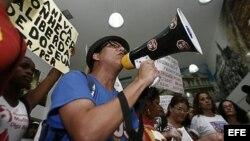 """Simpatizantes del régimen cubano gritan consignas y muestran carteles durante un evento para la exhibición del documental """"Conexión Cuba-Honduras"""", durante la visita de la cubana Yoani Sánchez."""