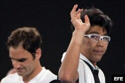 El tenista surcoreano Hyeon Chung (d) se despide del público tras tener que retirarse por sufrir ampollas en la parte inferior del pie izquierdo.